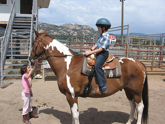 Kids riding horses safely.